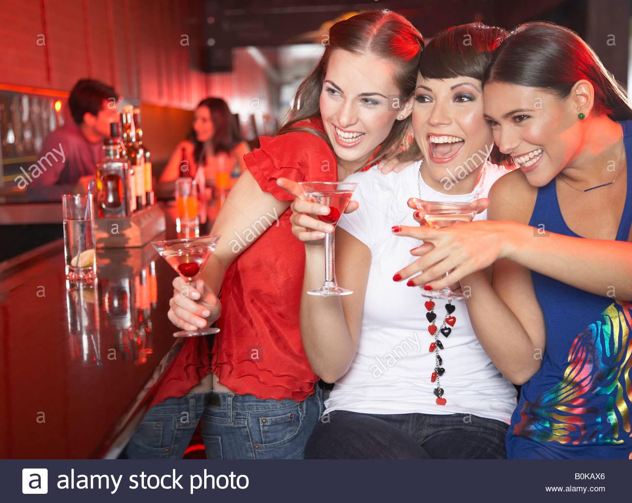Tre donne con bevande in discoteca di puntamento e sorridente Immagini Stock