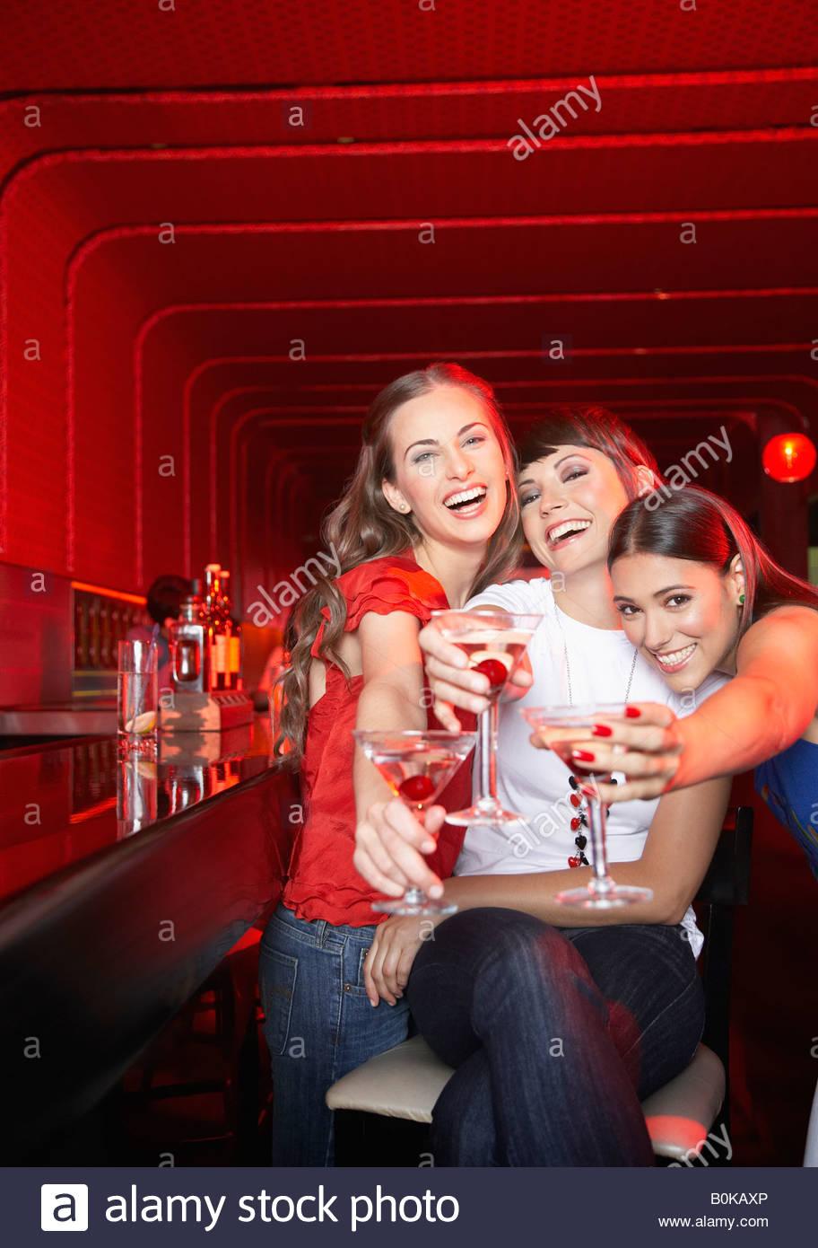 Tre donne con bevande in discoteca la tostatura e sorridente Immagini Stock