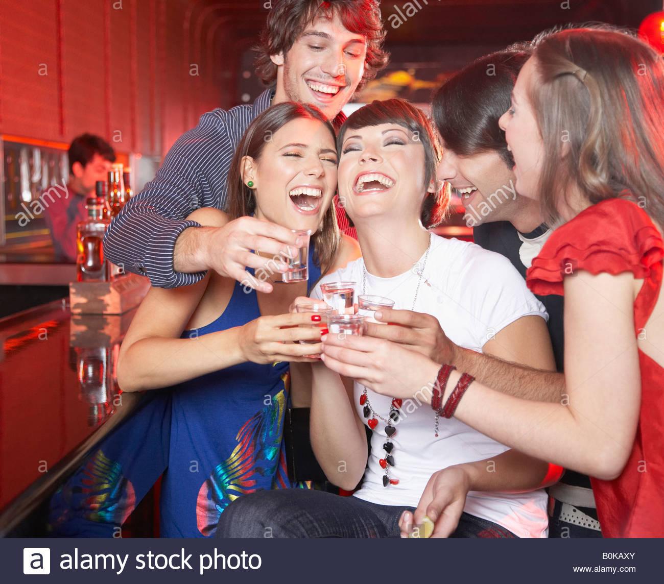 Cinque persone con scatti in discoteca la tostatura e sorridente Immagini Stock