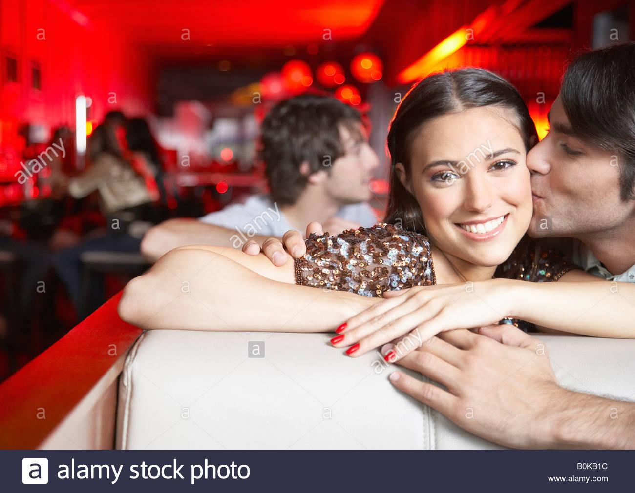 Giovane baciare in stand al nightclub e sorridente Immagini Stock