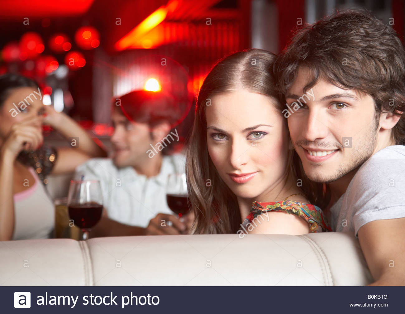 Giovane seduti insieme in stand al nightclub sorridente Immagini Stock
