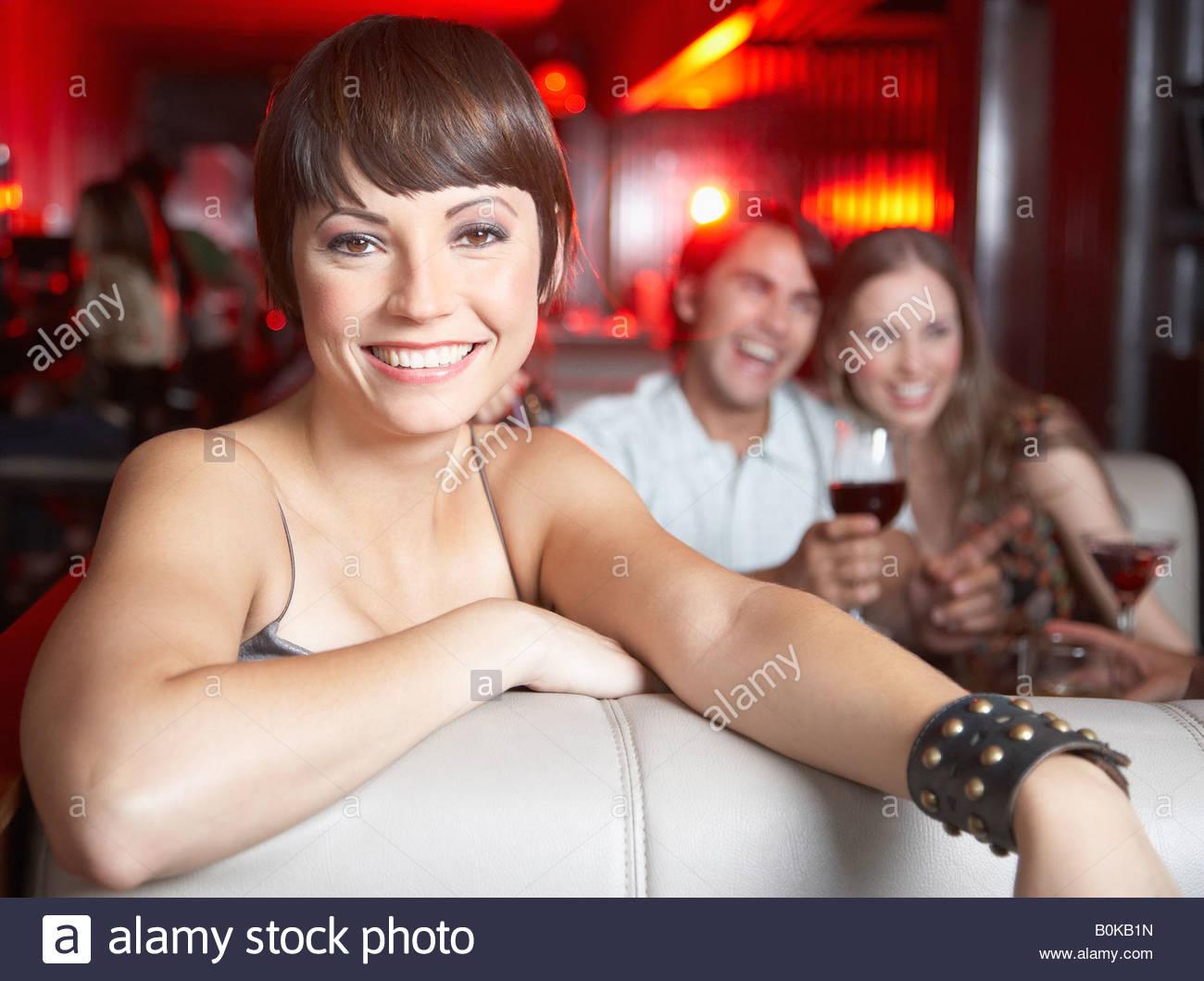 Donna seduta in stand al nightclub sorridente Immagini Stock