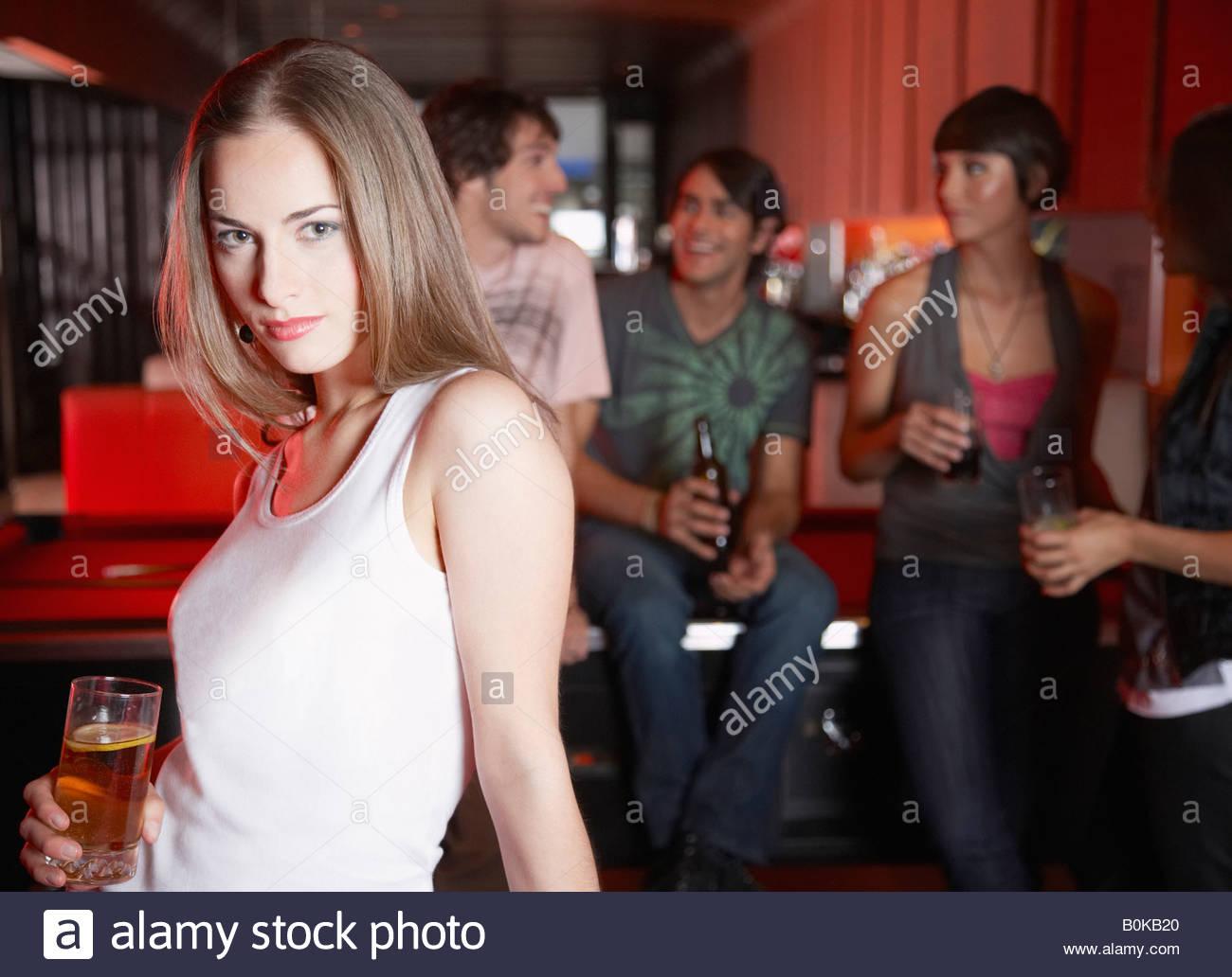 Donna con bevanda appoggiata sul tavolo da biliardo Immagini Stock