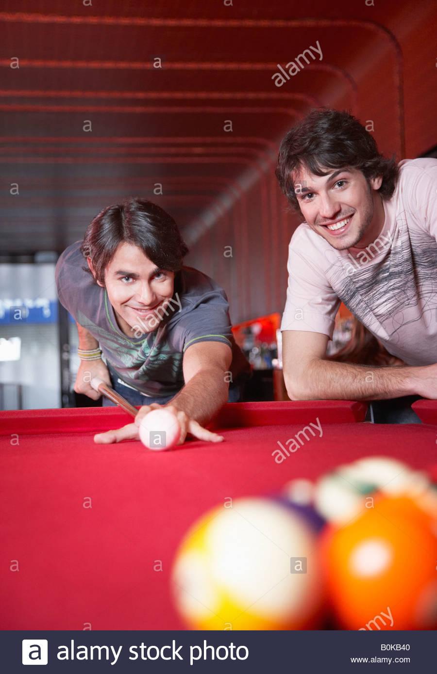 Due uomini giocando a biliardo e sorridente Immagini Stock