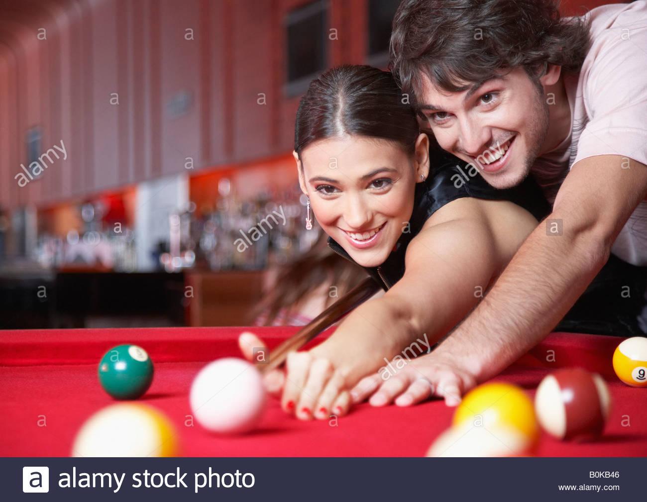 Giovane giocando a biliardo e sorridente Immagini Stock