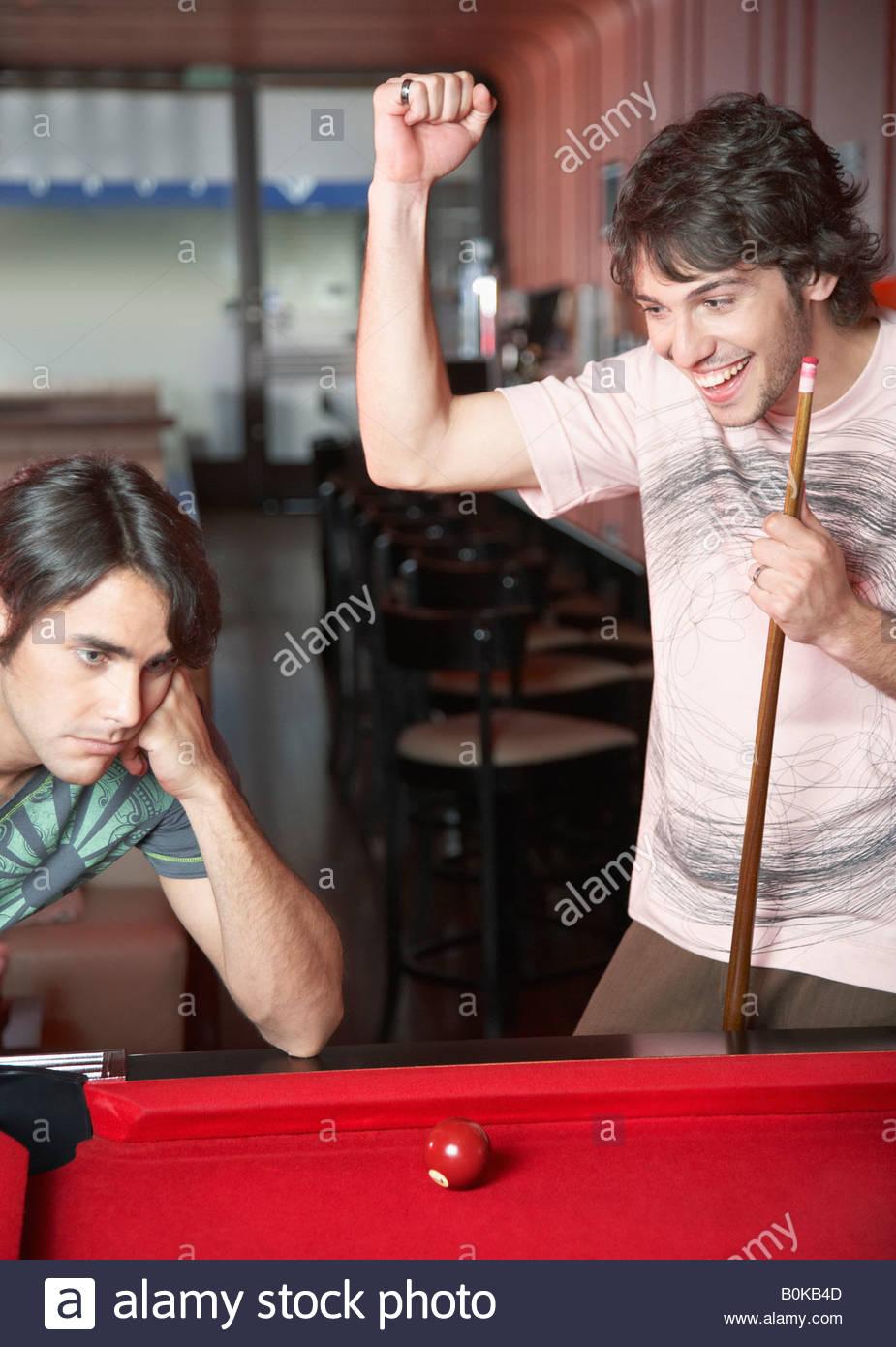 Due uomini giocando a biliardo con uno facendo un colpo vincente e sorridente Immagini Stock