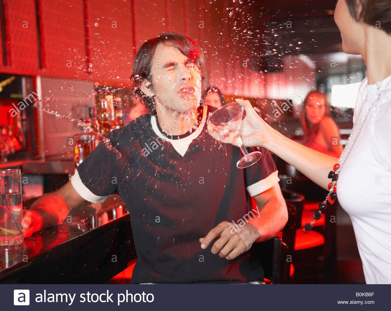 Donna in discoteca gettando la bevanda nel il volto dell'uomo Immagini Stock