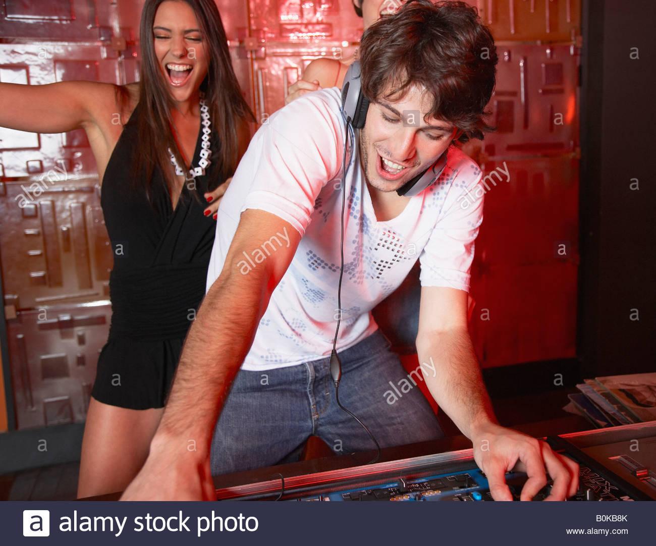 Disc jockey in discoteca con due donne che danzano dietro di lui sorridente Immagini Stock