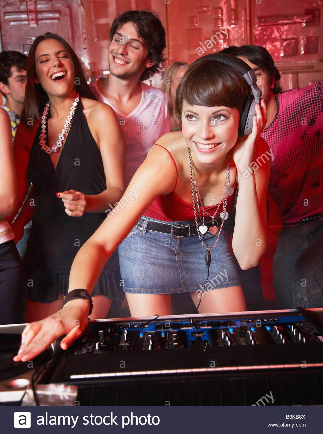 Disc jockey in discoteca con persone che ballano intorno a lei sorridente Immagini Stock