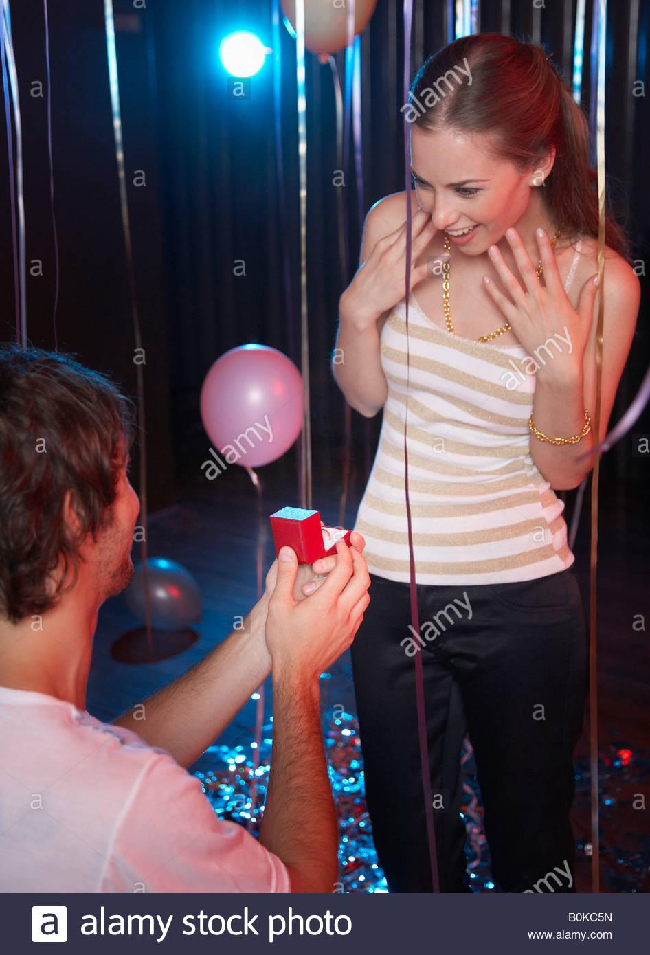 L'uomo propone di donna sorridente in discoteca Immagini Stock