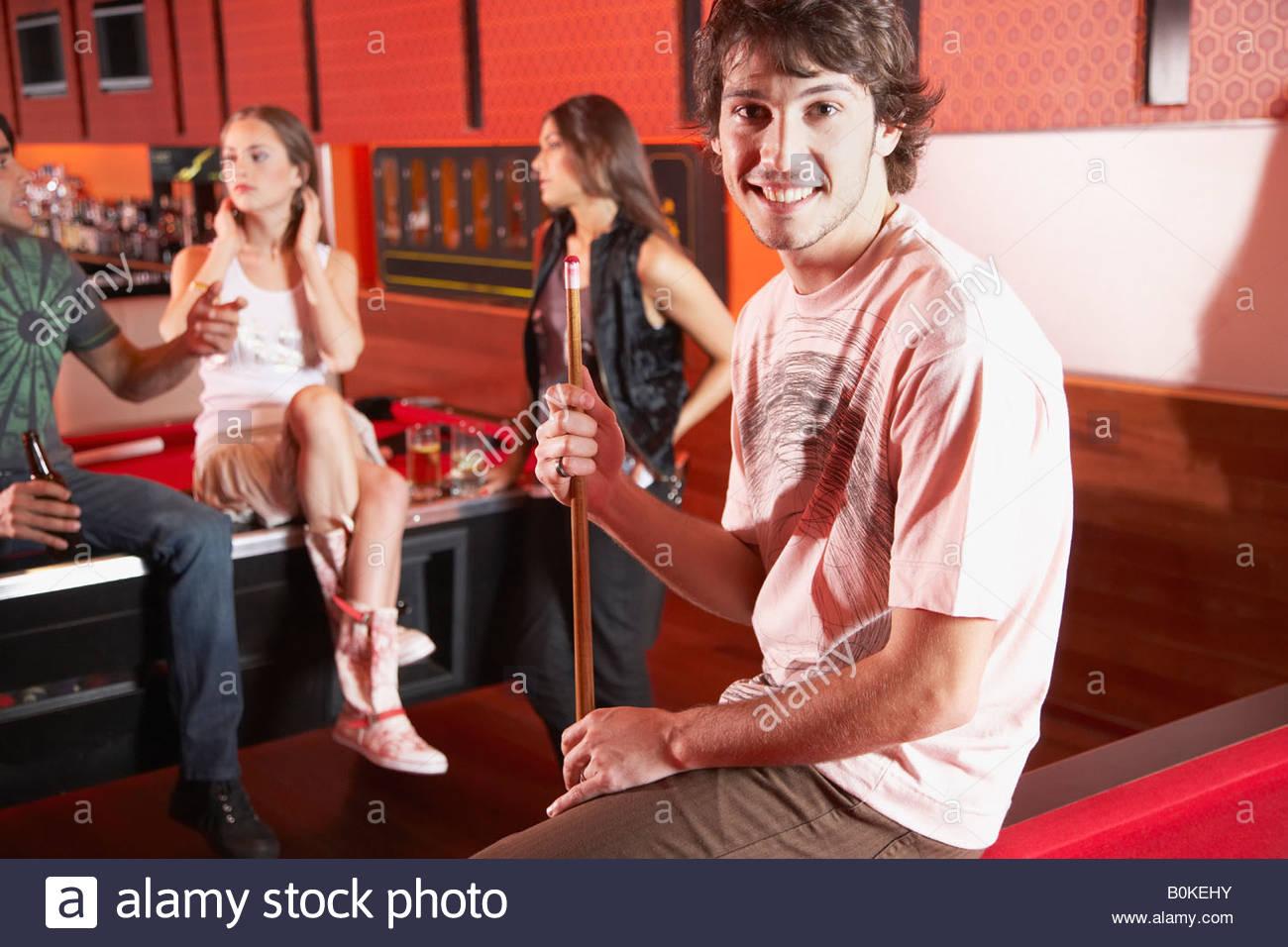Uomo seduto sul tavolo da biliardo sorridente e holding pool cue Immagini Stock