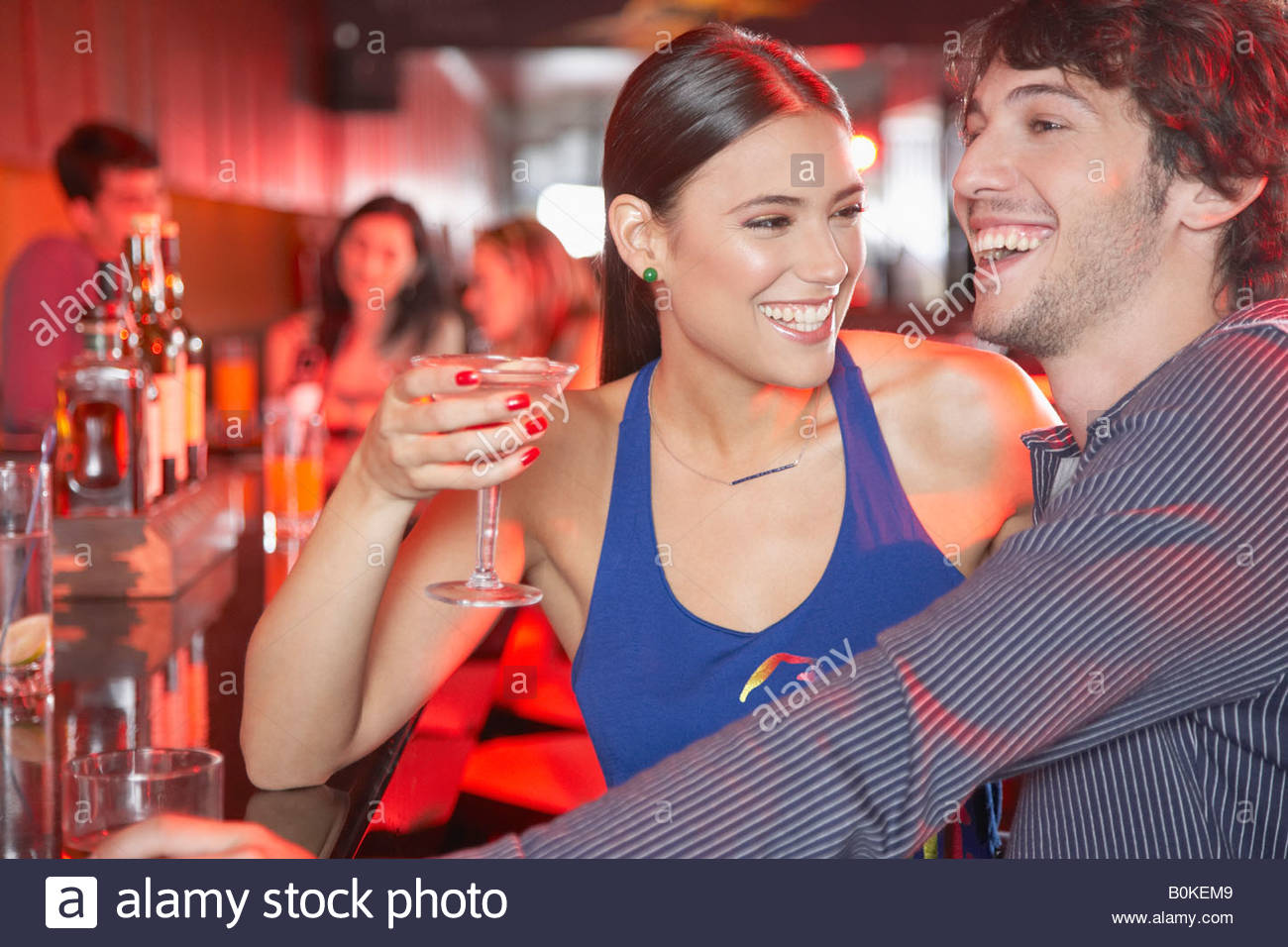 Matura in discoteca al bar con bevande sorridente Immagini Stock