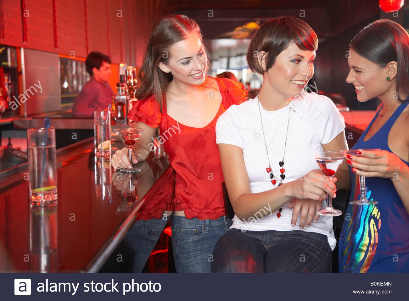 Tre donne in discoteca al bar con bevande la tostatura e sorridente Immagini Stock