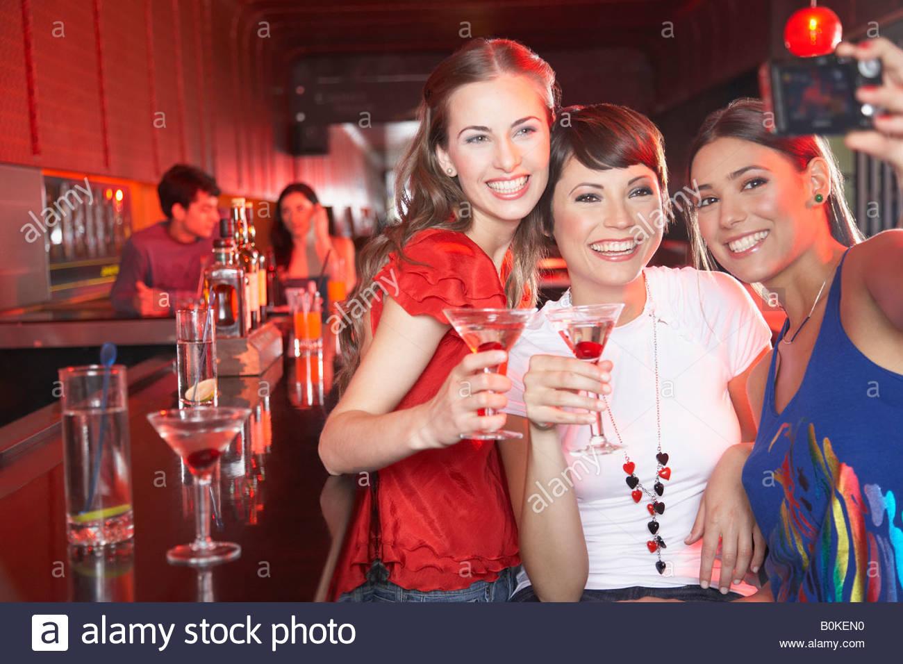 Tre donne in discoteca con bevande tenendo autoritratto con fotocamera digitale sorridente Immagini Stock