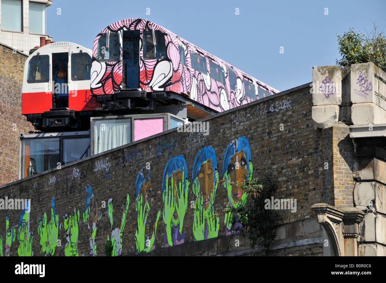 Il tubo di riciclo carrozze ferroviarie utilizzate come artisti sopra il vecchio viadotto ferroviario con pareti Immagini Stock