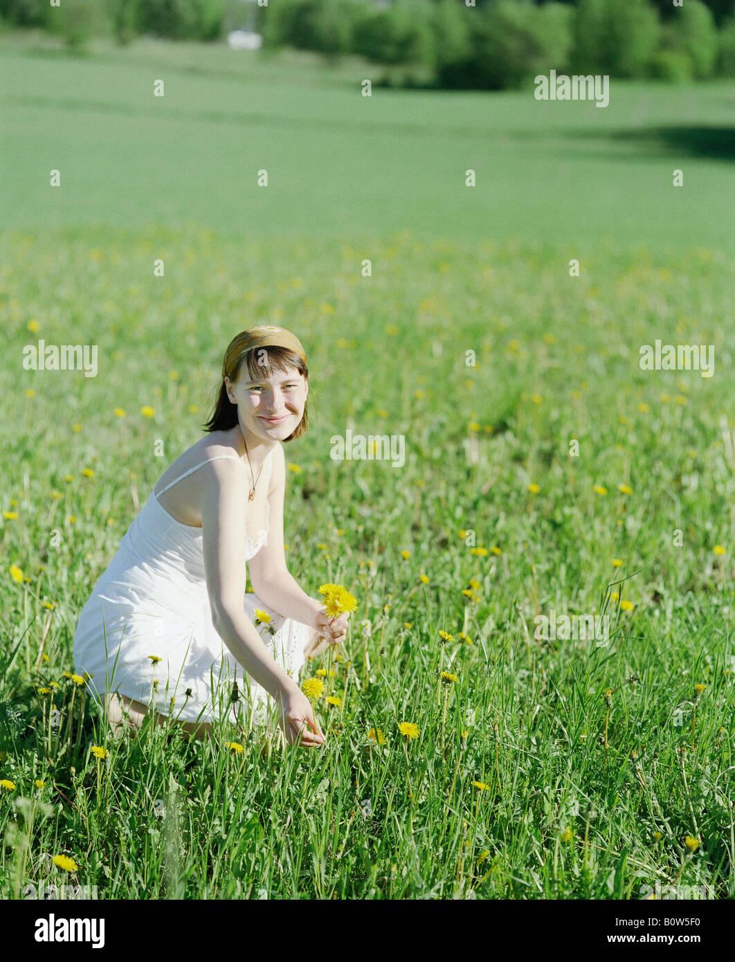 Giovane donna a caccia di fiori in un campo Immagini Stock