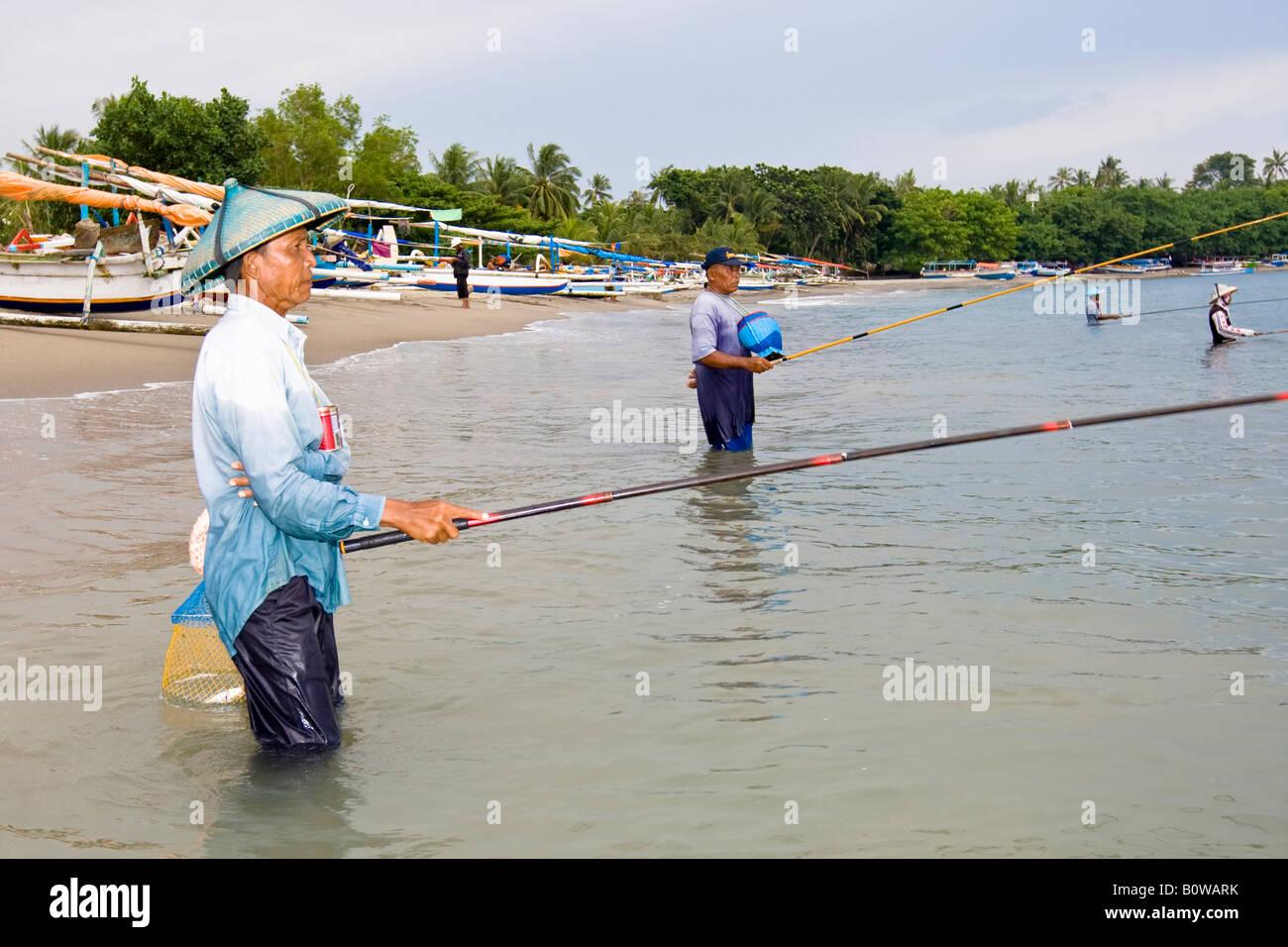 Vecchio Pescatore in piedi in mare nei pressi di Senggigi angling per piccoli pesci utilizzando i metodi tradizionali, Immagini Stock