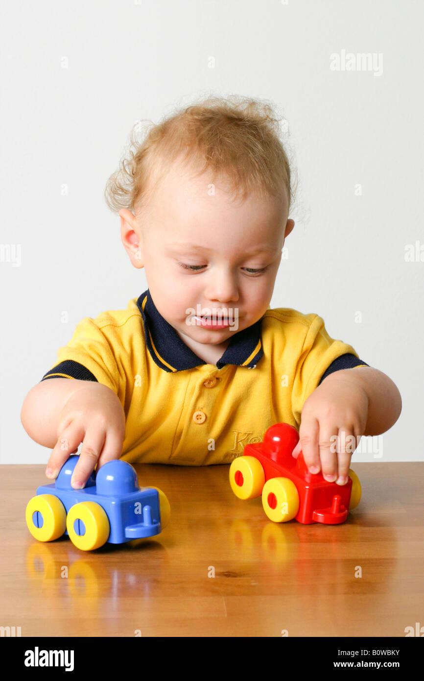 Uno-anno-vecchio ragazzo giocando con due automobili giocattolo Foto Stock