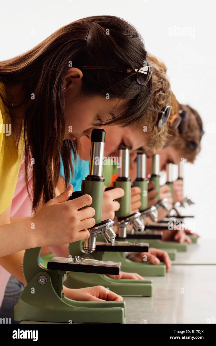 Un gruppo di ragazzi cercando in microscopi Immagini Stock