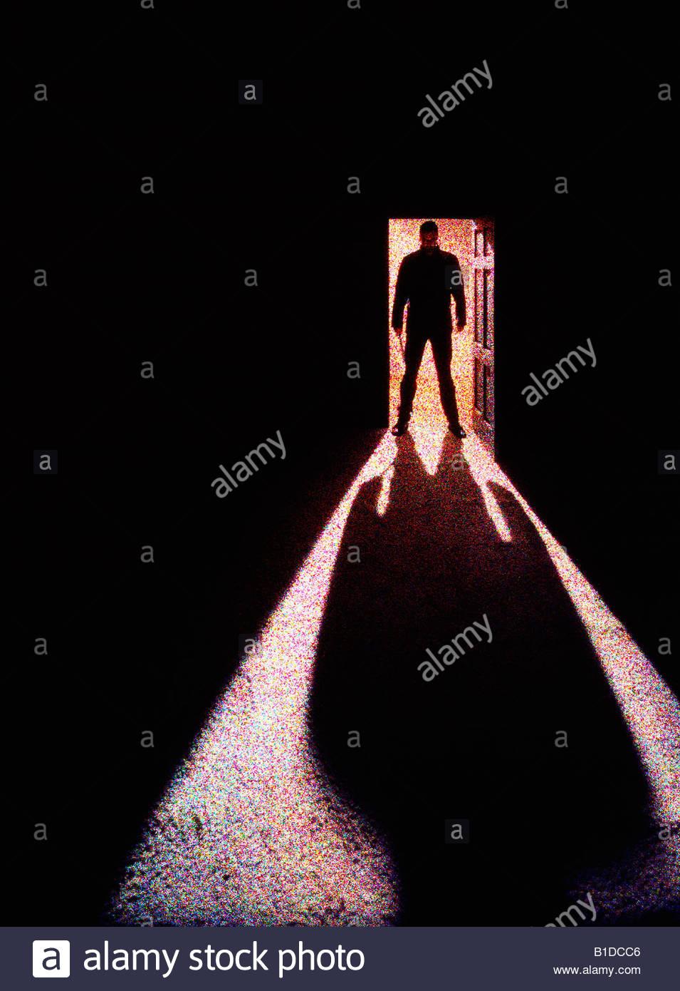 Una minacciosa la silhouette di un uomo in possesso di un coltello in una porta. Immagini Stock