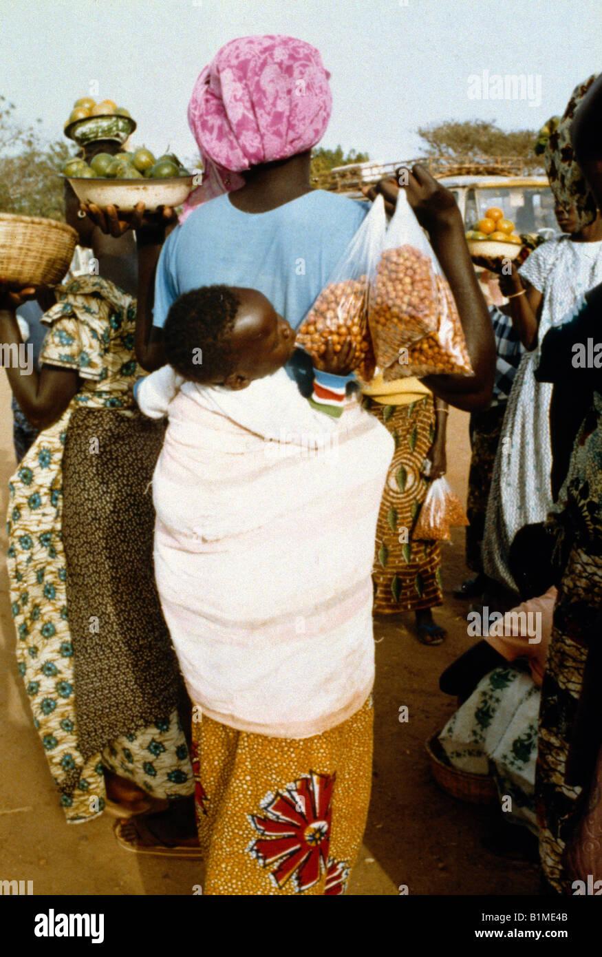 In Senegal la madre che porta il bambino sul retro Immagini Stock