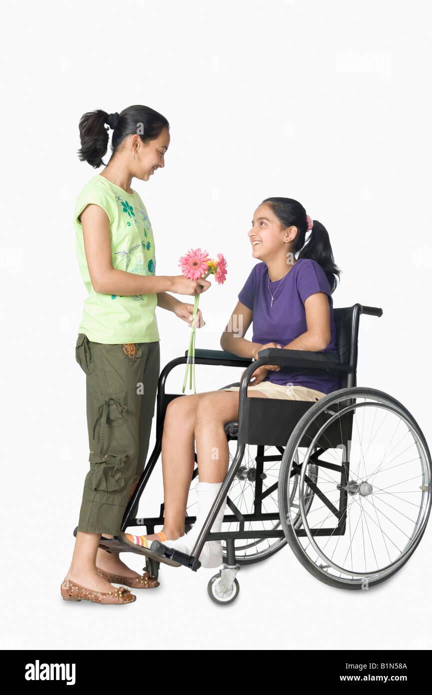 Ragazza dando ai fiori di sua sorella seduto in una sedia a rotelle Immagini Stock