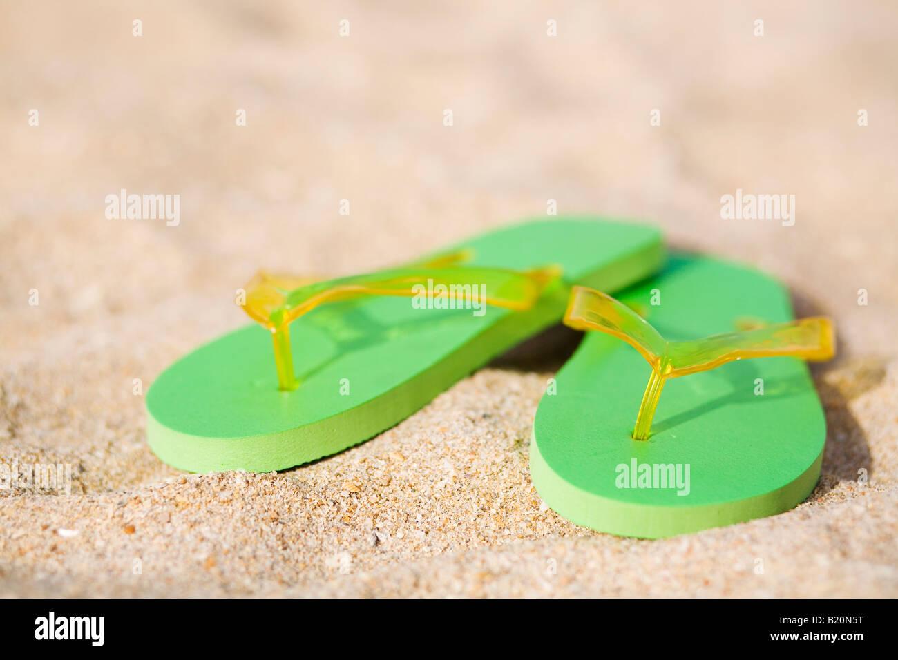 Coppia di green flip flop sulla spiaggia. Immagini Stock