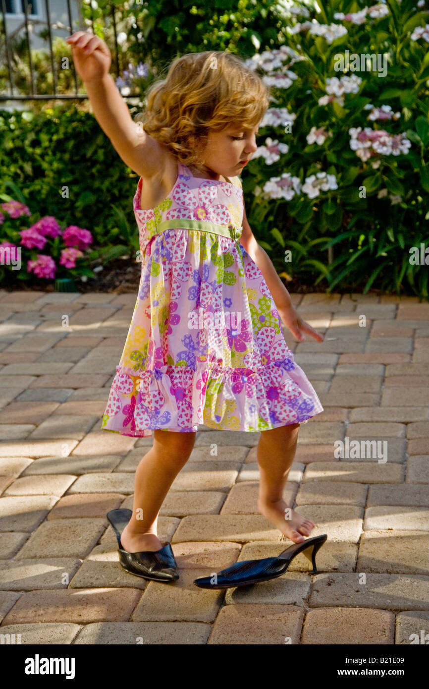 A due anni di ragazza cerca su sua madre s scarpe a casa nel sud della California Foto Stock