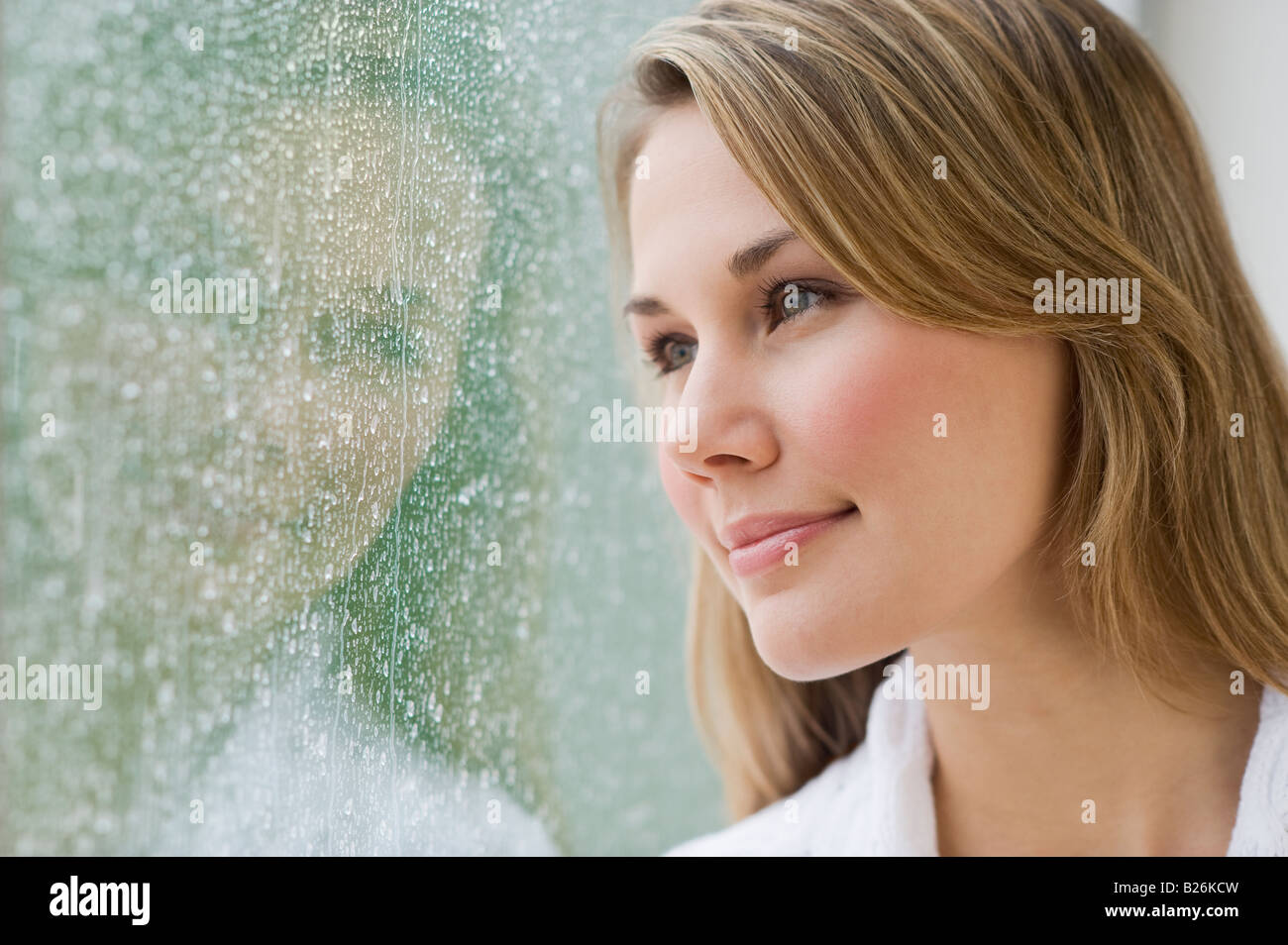 Donna che guarda fuori la finestra delle piogge Immagini Stock