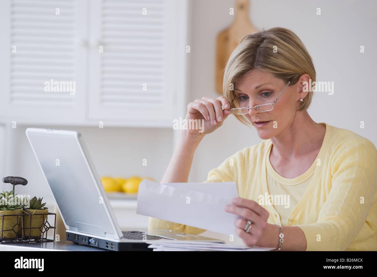 La donna la lettura della posta accanto al laptop Immagini Stock