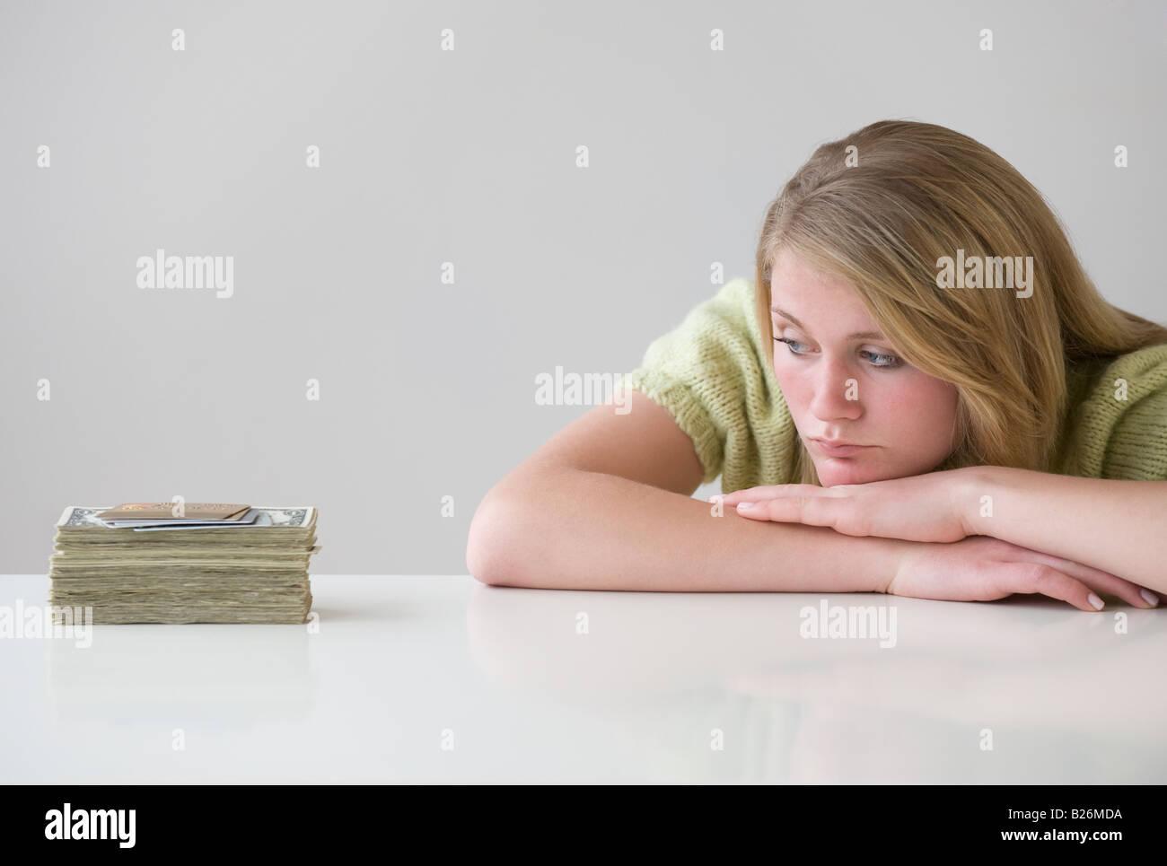 Ragazza adolescente guardando alla pila di denaro Immagini Stock