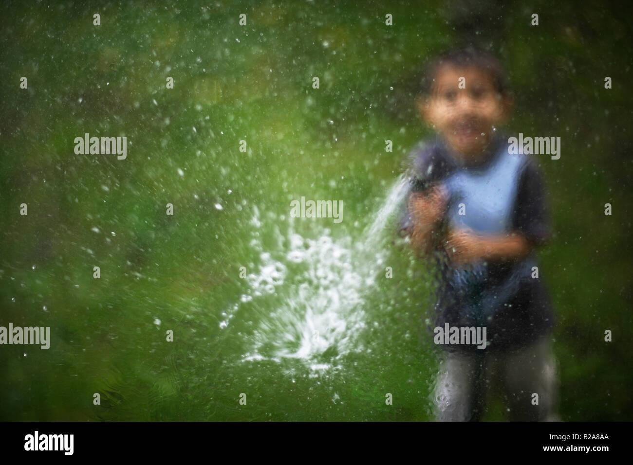 Tubo flessibile spruzzata in una finestra di vetro 6 anno vecchio ragazzo razza mista indiano caucasico etnica Immagini Stock