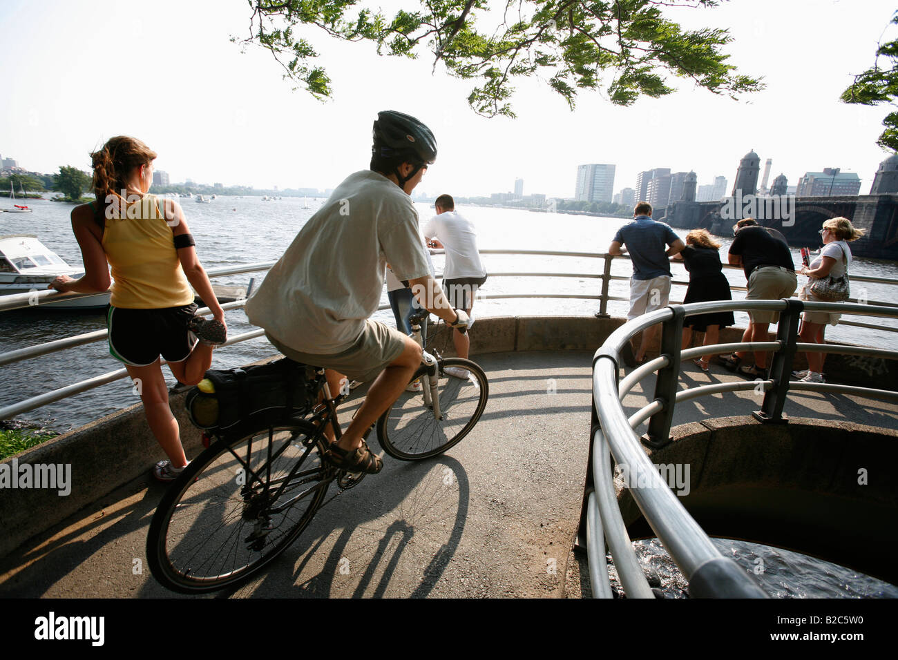 Un pareggiatore ciclista e i pedoni sono visto su un marciapiede sulle rive del fiume Charles a Boston Immagini Stock