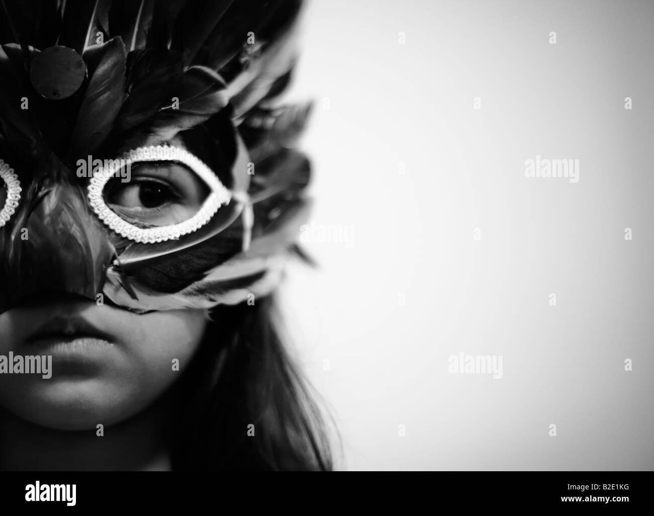Bambina di cinque anni indossa un costume di piume maschera Immagini Stock