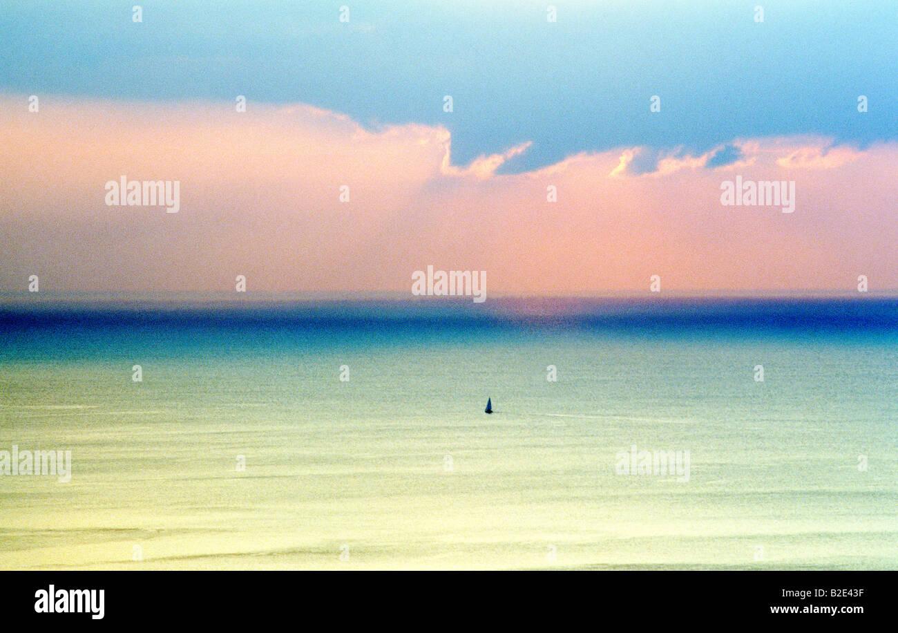 Lone yacht a vela attraverso la calma il mare aperto oceano in serata. La luce del mattino Immagini Stock