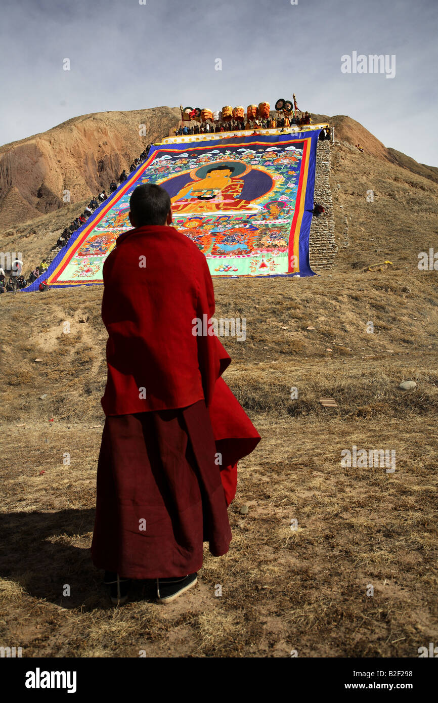 Un monaco buddista sta pregando davanti a un enorme Thangka Immagini Stock