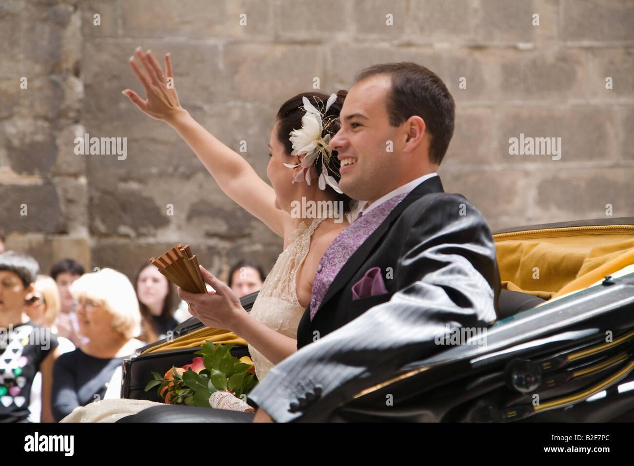 Spagna Toledo sposa e lo sposo nel retro del carro trainato da cavalli lasciare la chiesa e corteo lungo una strada Immagini Stock
