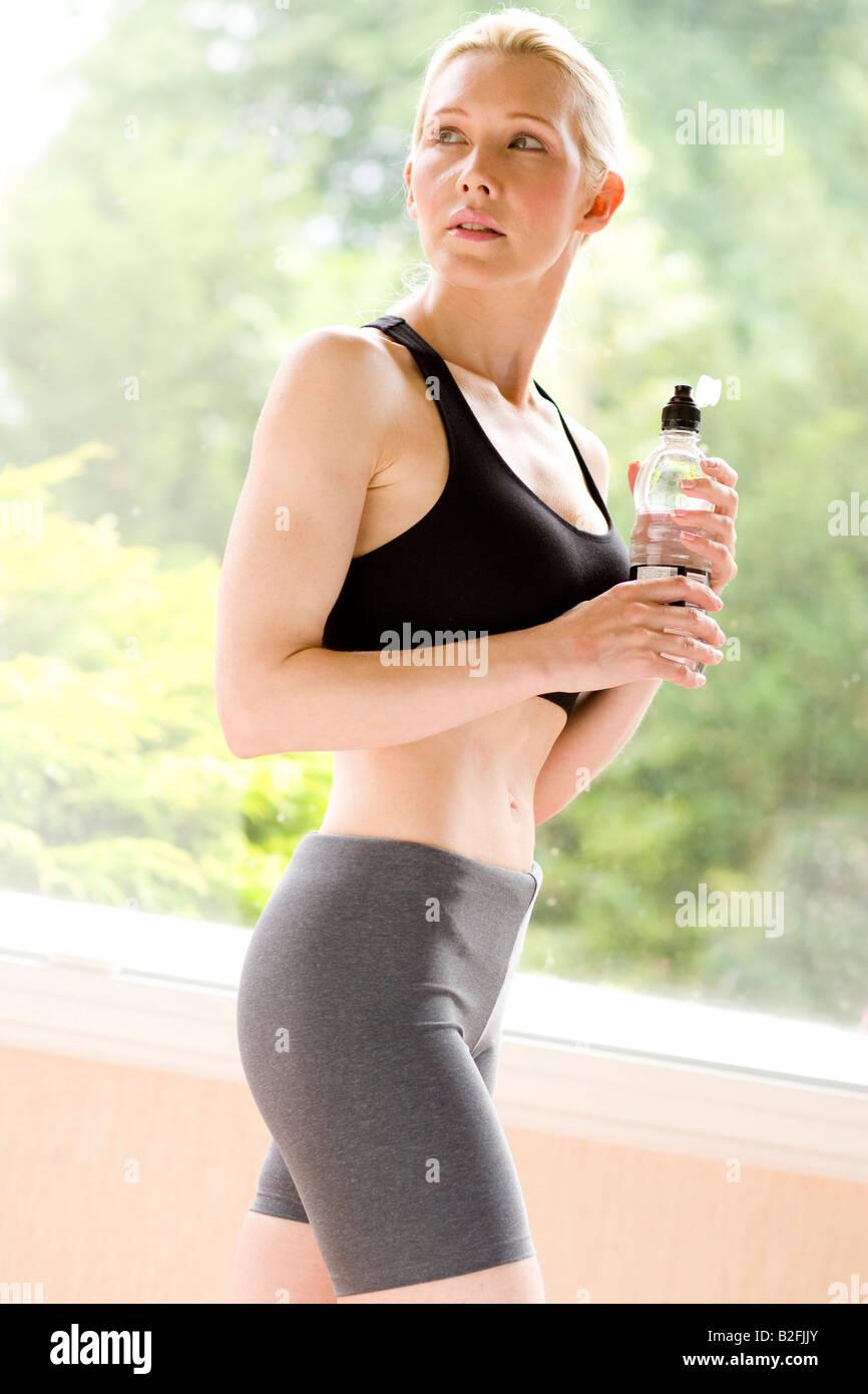 La donna a indossare abbigliamento sportivo con acqua in bottiglia Immagini Stock
