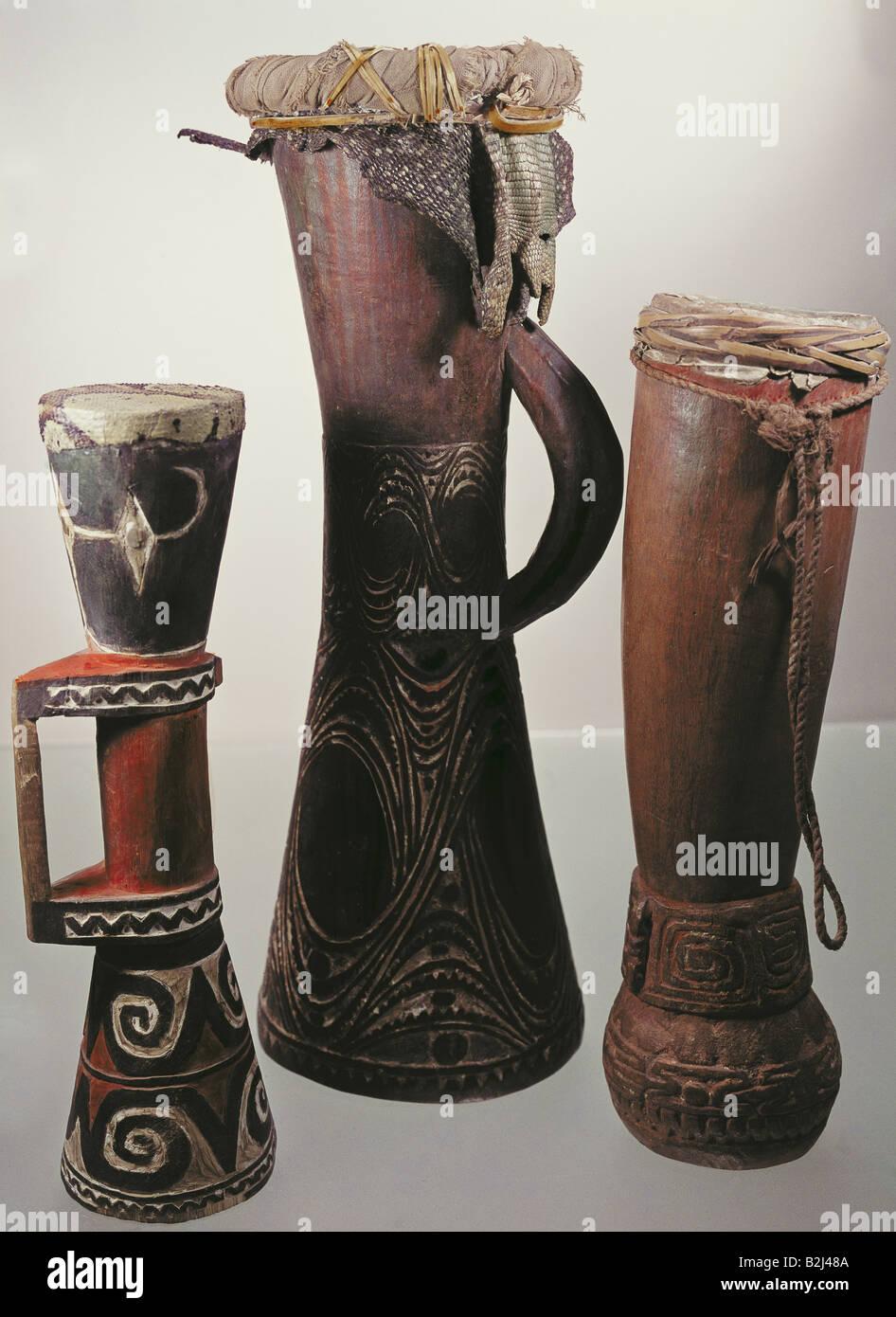 Musica, strumenti, tre di clessidra-tamburi sagomato, legno, ornata, dipinti, iguana pelle, snakeskin, Nuova Guinea, Immagini Stock