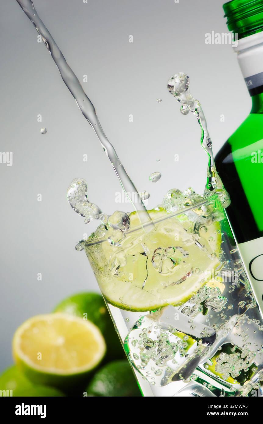 Gin Tonic schizzi in vetro con bottiglia di lato Immagini Stock