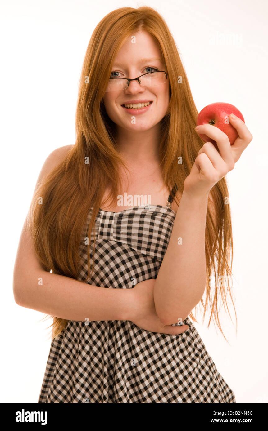 Dai capelli rossi 17 18 19 anno vecchio slim bella ragazza adolescente azienda Apple sorridenti che indossano occhiali Immagini Stock