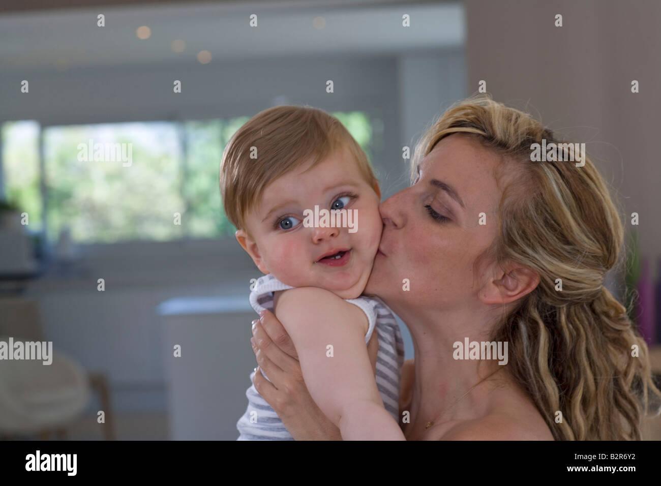 Madre bacia il bambino a casa Immagini Stock