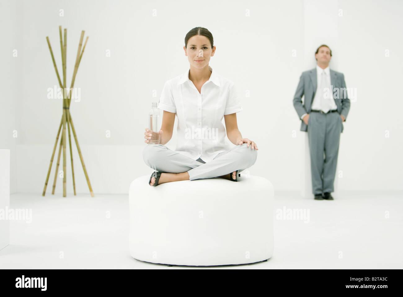 Professional donna seduta su ottomano, tenendo la bottiglia di acqua, imprenditore e bambù in background Immagini Stock