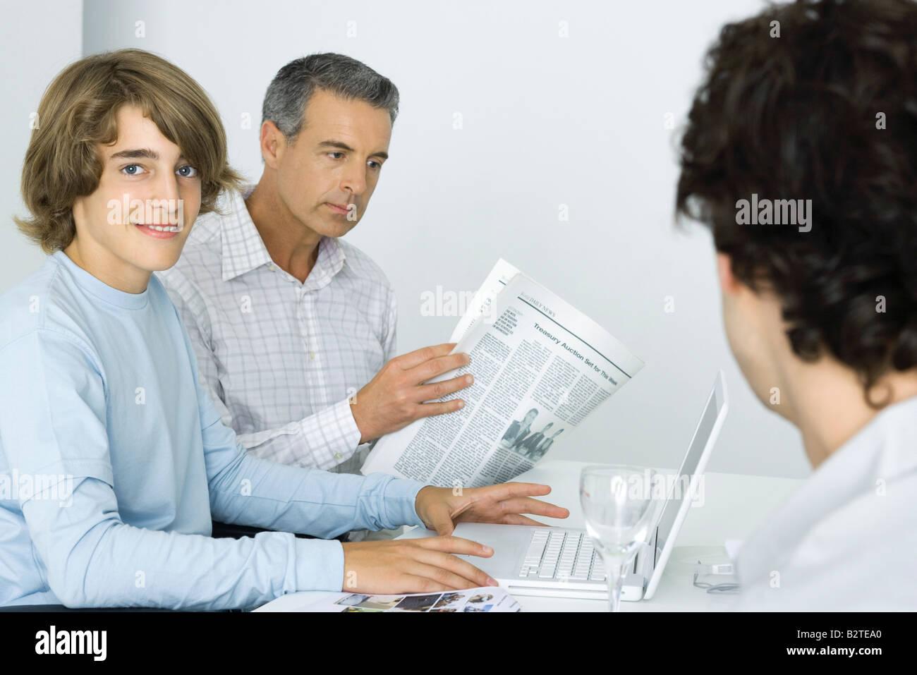 Teen boy a tavola con padre, utilizzando il computer portatile, uomo quotidiano di lettura Immagini Stock