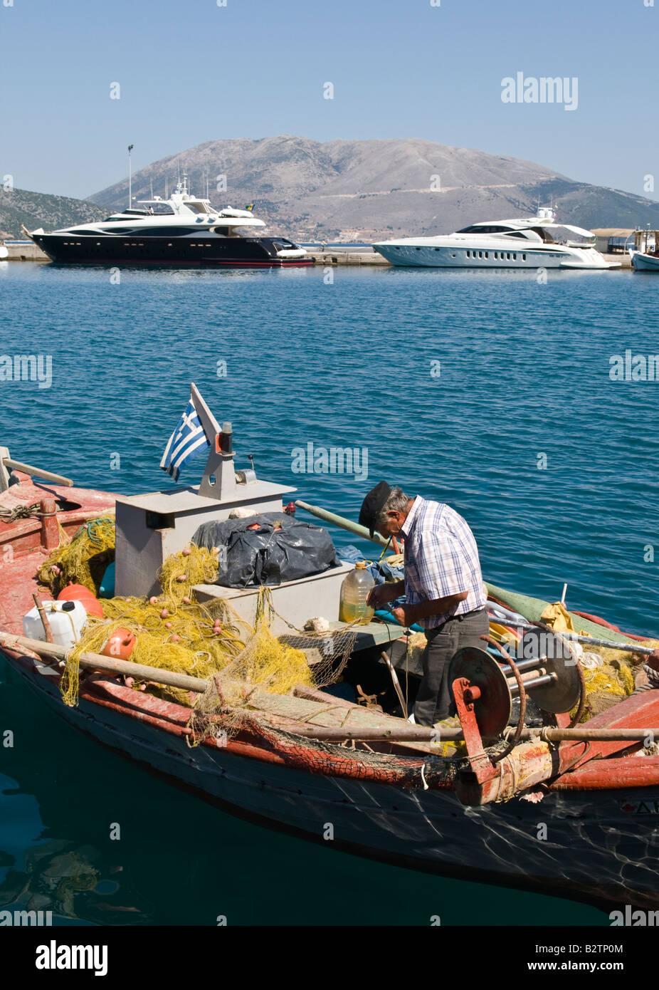 Yacht di lusso e semplici barche da pesca condividere il porto di Sami Kefalonia in Grecia Immagini Stock