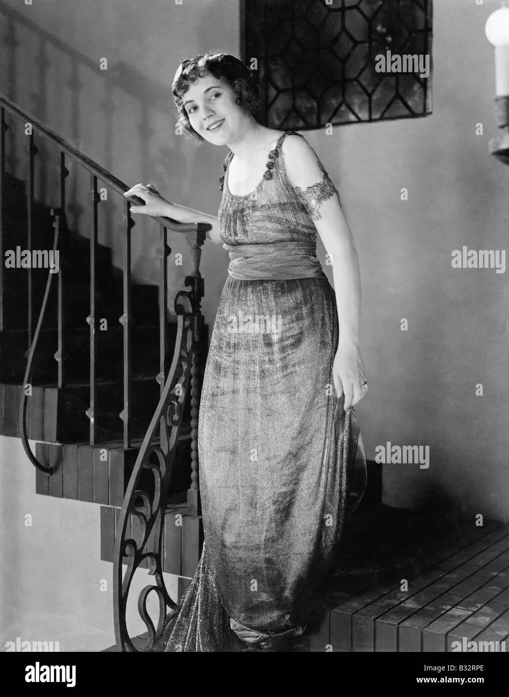 Giovane donna si sta spostando verso il basso di una scala e sorridente Immagini Stock