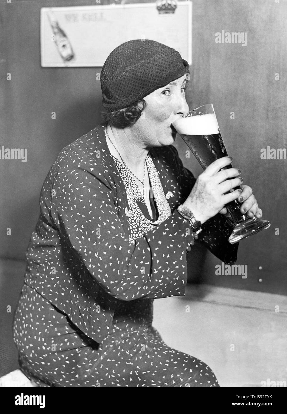 Donna di bere al di fuori di un grande bicchiere di birra Immagini Stock