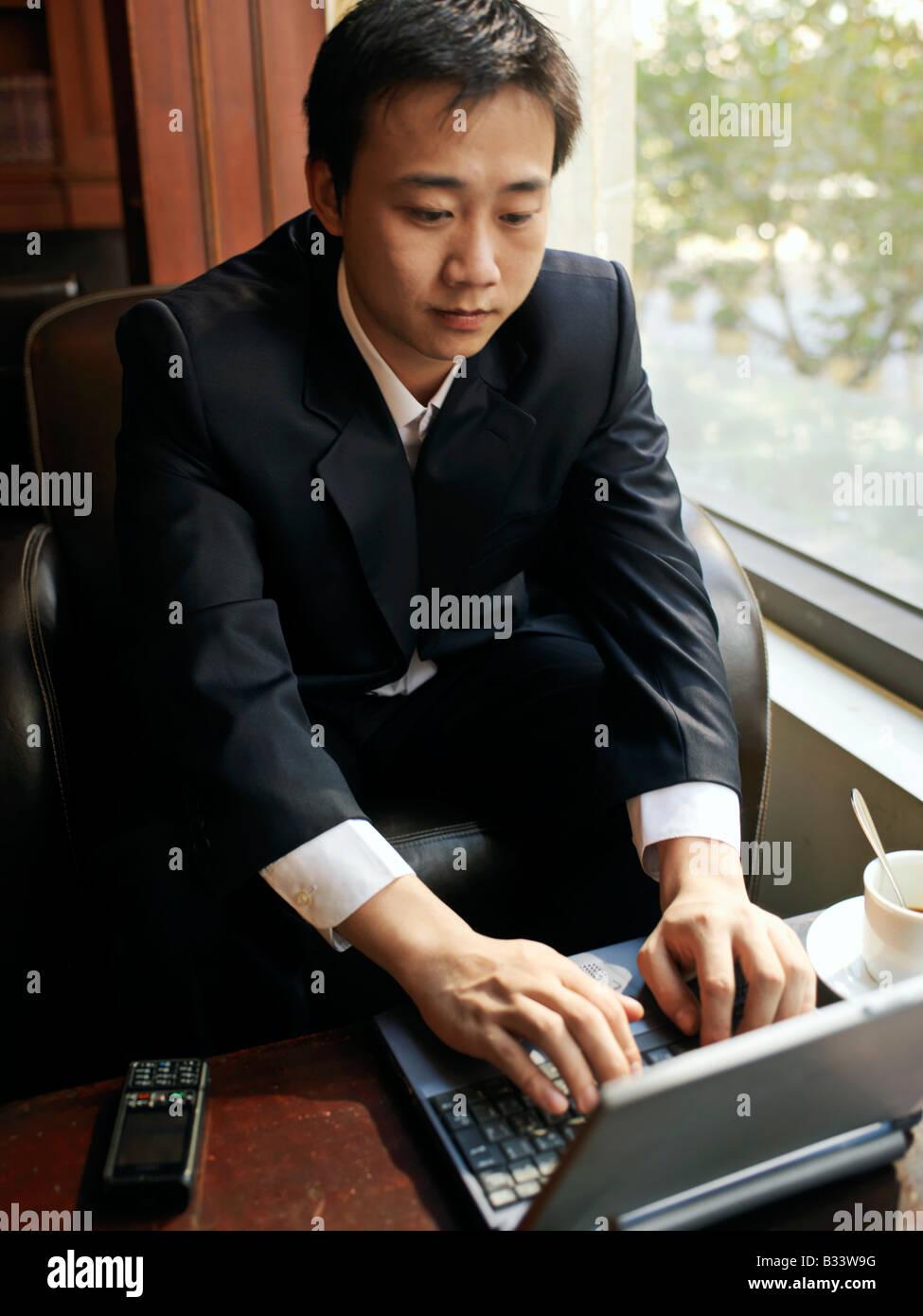 L uomo si siede da una finestra utilizzando il suo computer portatile per la comunicazione Immagini Stock