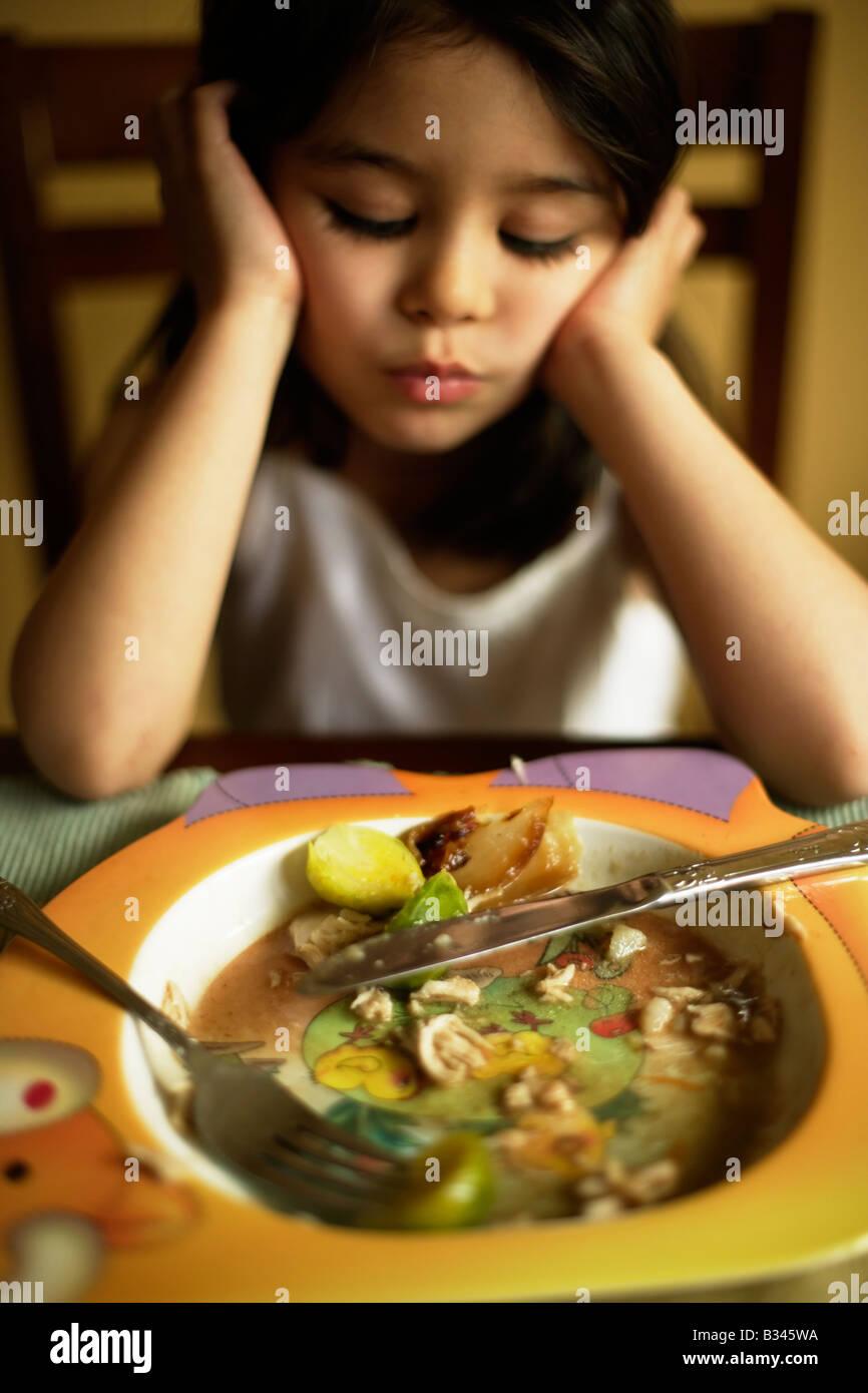 Bambina di cinque anni diventa choosey circa il suo cibo e decide che non gli piace mangiare i cavoletti di Bruxelles Immagini Stock