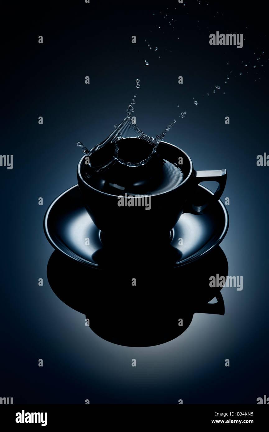 Spruzzi di acqua al di fuori della tazza di caffè Immagini Stock